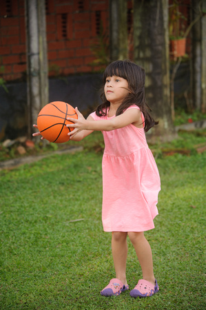 Nur Eryna and Qamelia playing basketball in garden